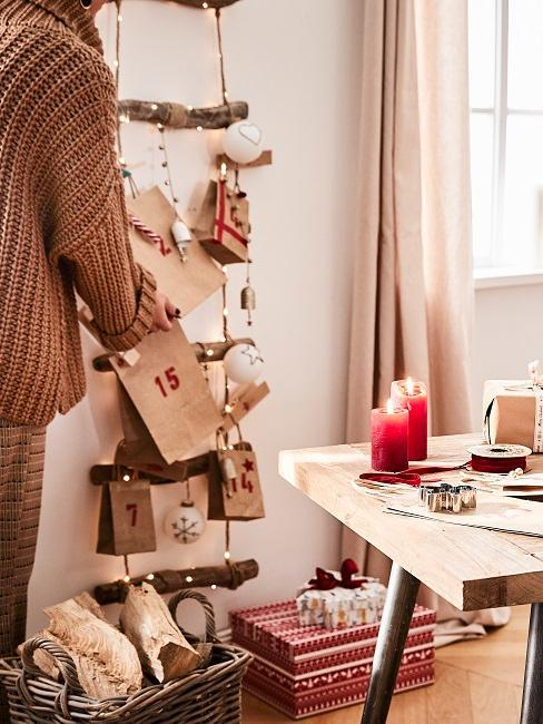 Drewniany stół z czerwonymi świecami. Na ścianie kalendarz adwentowy DIY