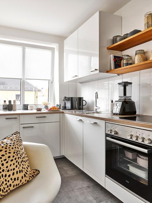Biała kuchnia z drewnianym blatem, beżowym fotelem z poduszką, półkami i sprzętami