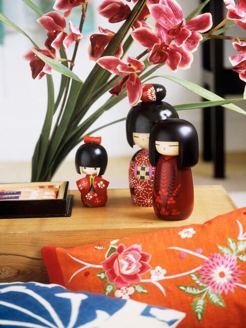 Figurki kokeshi na drewnianym stoliku przy wazonie z kwatami