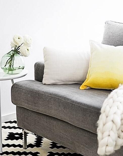 Szara sofa z biała poduszką oraz żółta poduszką we wzór ombre na biało - czarnym dywanie