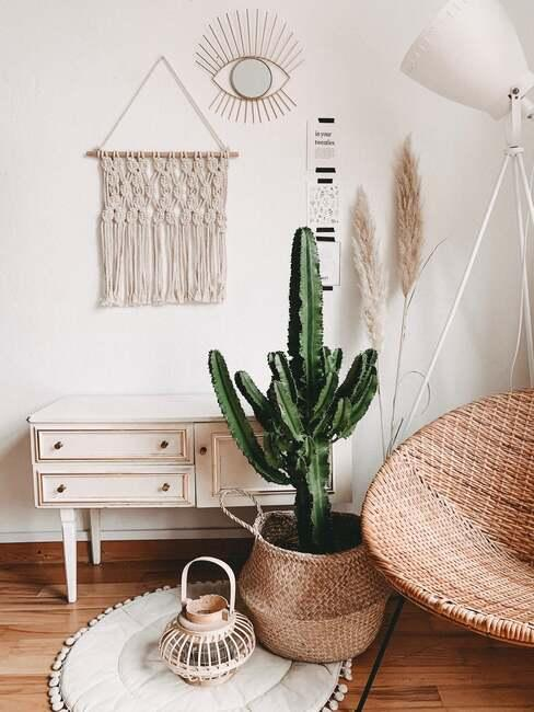 Białe wnętrze z szafką, rośliną, hamakiem, trawą pampasową oraz makramą na ścianie