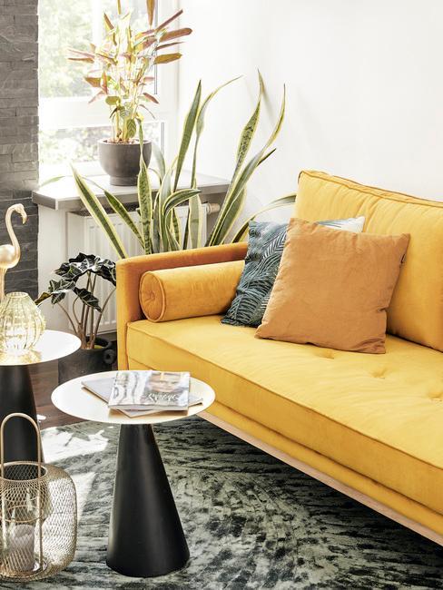 Salon w stylu retro z żółtą sofą, dwoma stoliczkami oraz wężownica w rogu