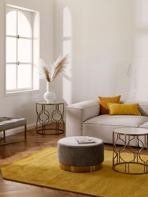 salon z białą sofą, żółtymi poduszkami, zółtym dywanem, stolikami kawowymi oraz pufem