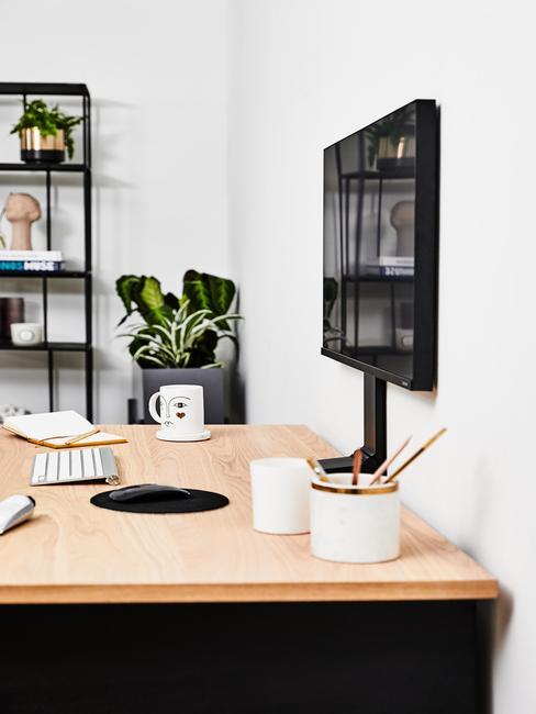 wnętrze biura z drewnianym biurkiem, monitorem, czarną, metalową otwarta półką oraz roślinami w doniczkach