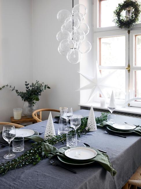 Stół z szarym obrusem, zastawą z Westwing Collection, zielonymi serwetkami oraz gałęzią świerku jako dekoracja