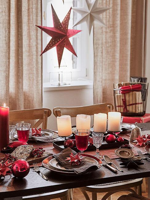 Drewniany stół z czterema białymi świecami, zastawą sotłową z Westwing Collection oraz dekoracje