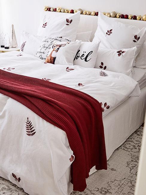 Łóżko z pościelą w świąteczne wzory oraz czerwonym, pledowym kocem
