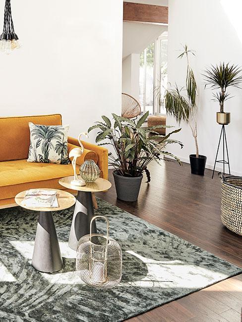 Salon z żółtą sofą z aksamitu otoczona roślinami i motywami roślinnymi