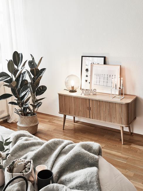 Salon w stylu boho z komodą z jasnego drewna i fikusem w doniczce