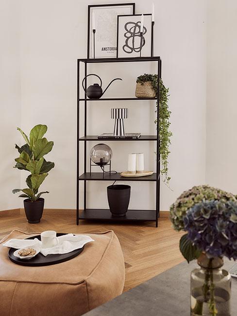 Czarny regał w jasnym salonie z dekoracjami, konewką i roślinami