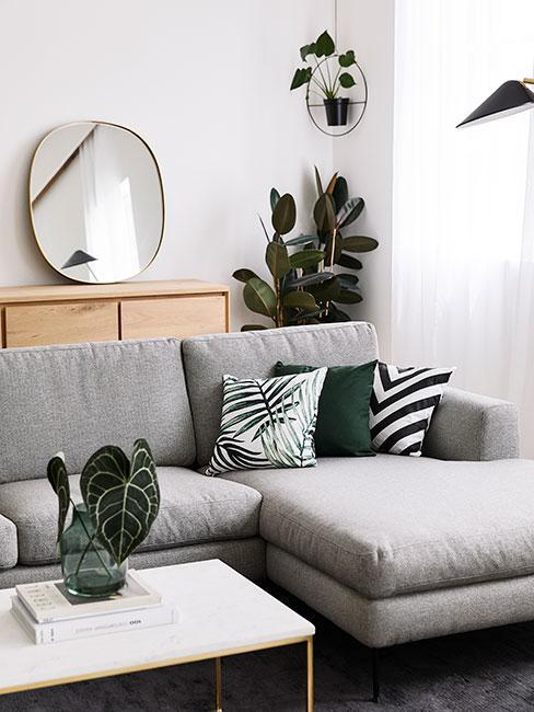 Salon z szarą sofą, zielonymi poduszkami i roślinami