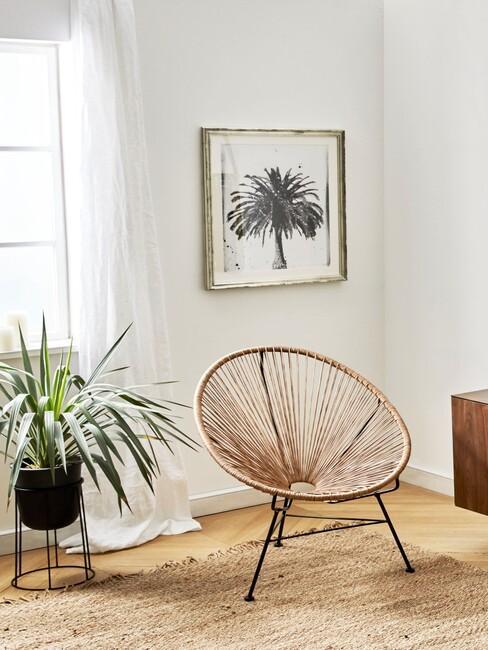 zbliżenie na fotel w stylu boho z rattanu, obraz na ścianie oraz dracenę w dużej, czarnej doniczce
