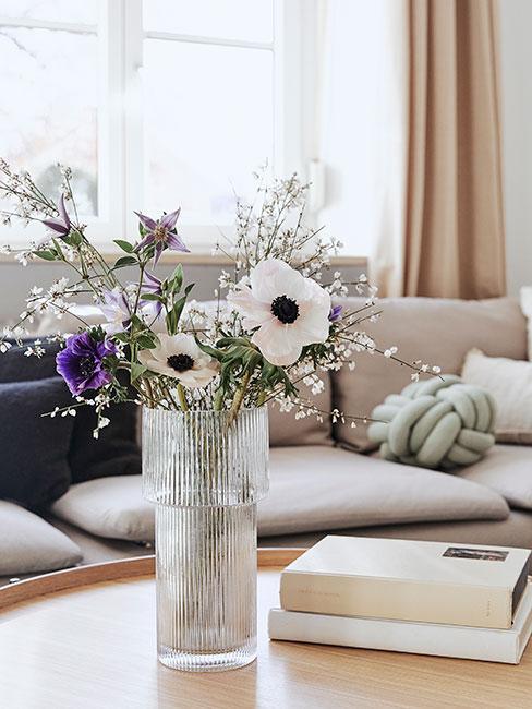 bukiet białych i fioletowych kwiatów w szklanym wazonie na tle szarej sofy