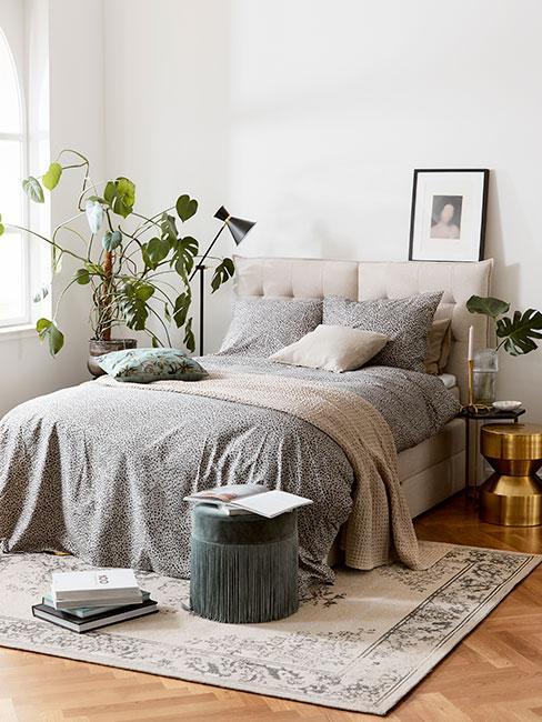 Sypialnia z szarym dywanem vintage, zielonym pufem i monsterą