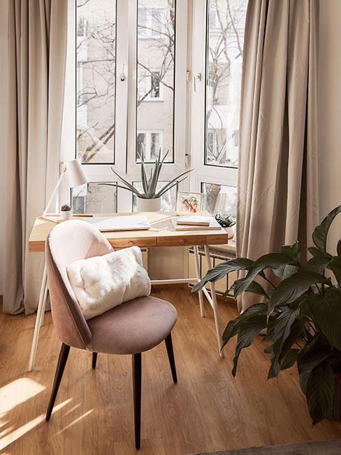 Biurko z jsnego drewna przy oknie obok rożowego krzesła z aksamitu