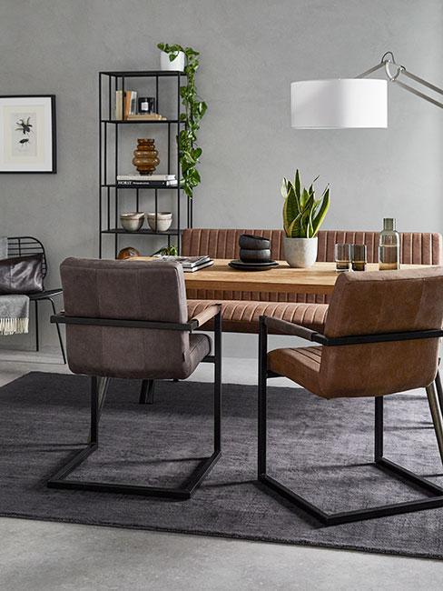 Jadalnia w stylu industrialnym brązowymi i szarymi krzesłami ze skóry i czarnym metalowym regałem z roślinami
