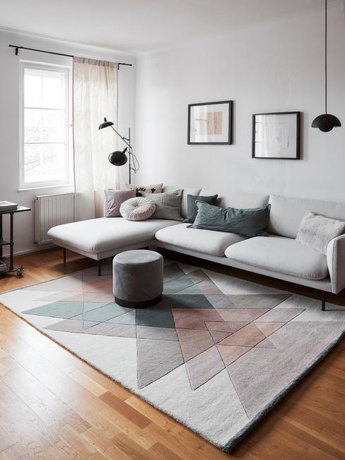 Szary salon z wzorzystym dywanem, szarym pufem, poduszkami i galerią ścianną
