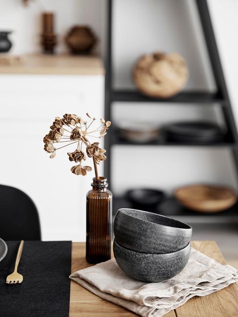 Zbliżenie na drewniany stół z czaernmi miseczkami, wazonem w jadalni
