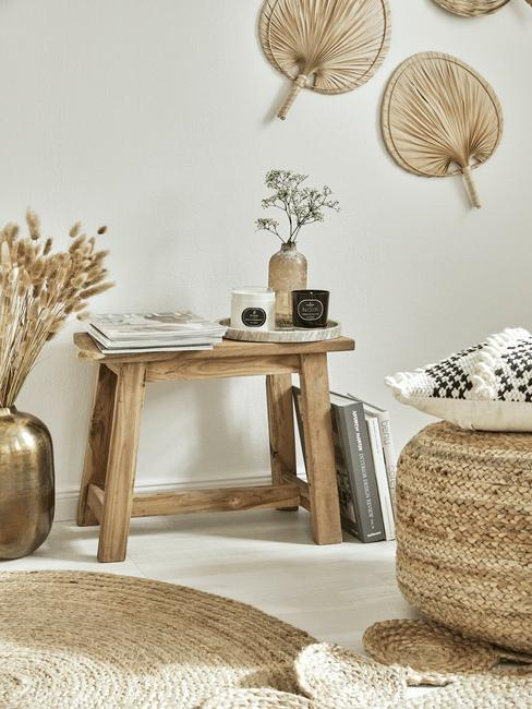 Zbliżenie na drewnianą ławkę, rattanwy puf oraz złoty, metalowy wazon