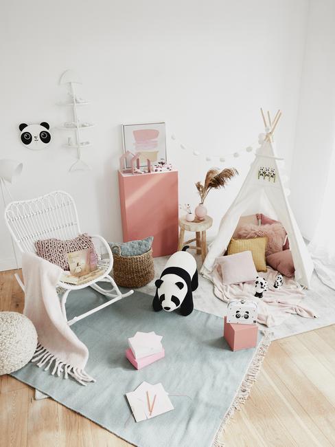 Kącik do zabawy w pokoju dziecięcym z namiotem, niebieskim dywanem, białym fotelem bujanym oraz zabawkami