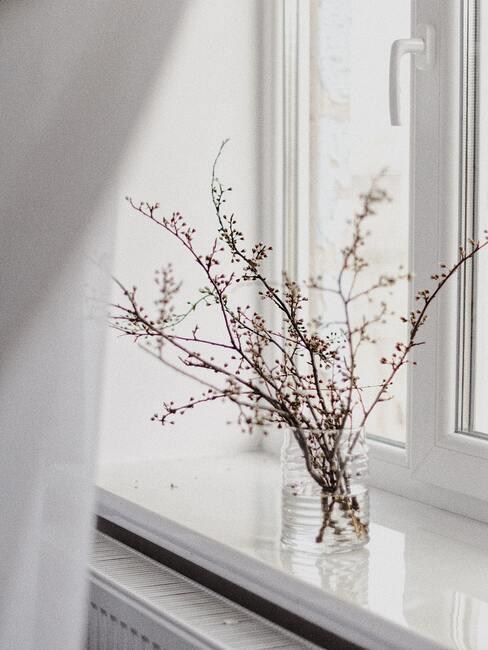 delikatne kwiaty w wazonie na parapecie w stylu ikebana