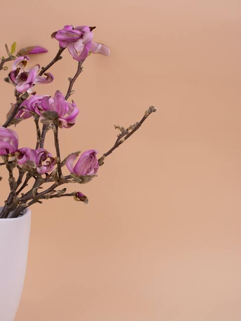 rózowe kwiaty w białym wazonie w stylu ikebana