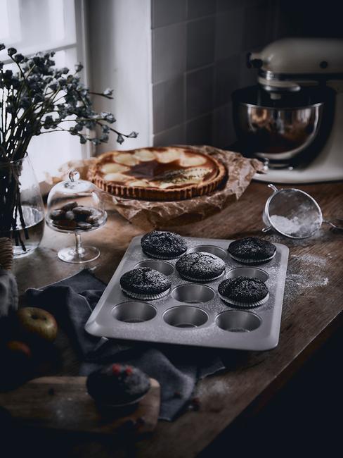 Czekoladowe babeczki w blaszcze na muffiny na drewnianym blacie w kuchni