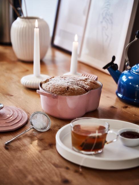 Drewniany stół z niebieskim czajnikiem, różowym, żeliwnym garnkiem z ciastem i tacą z herbata i dżemem