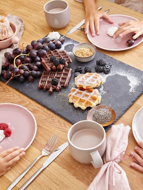 Fragment stołu z tacą śniadaniową z goframi, talerzami śniadaniowymi i kubkami