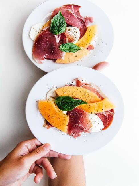 melon z szynka parmeńską na białym talerzu