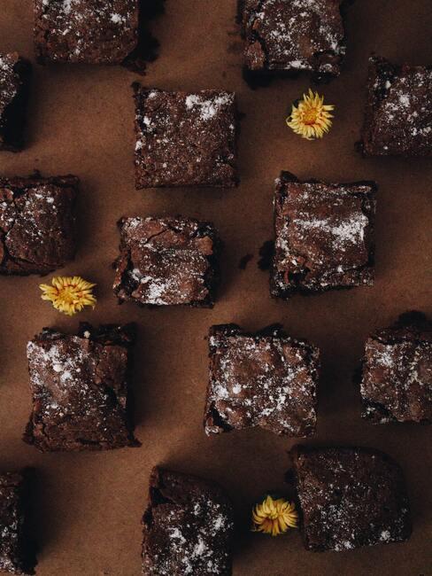 brownie ułozone na czekoladowym tle, ozdobione żółtymi kwiatami