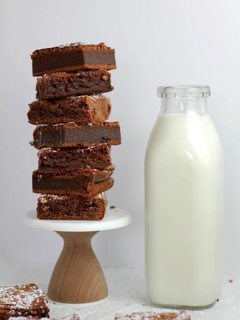 Brownie ułożone w stos na paterze, butelka mleka obok