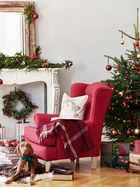 Czewrony fotel uszak w świątecznym salonie obok psa, kominka i choinki z czerwonymi i złotymi bombkami