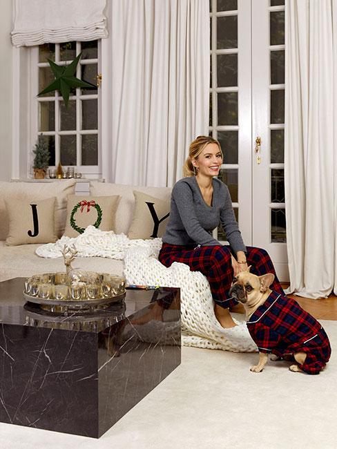 Kobieta z włosami blond ubrana w piżamę w szkocką kratę w świątecznym salonie z mopsem w ubranku w szkocką kratę