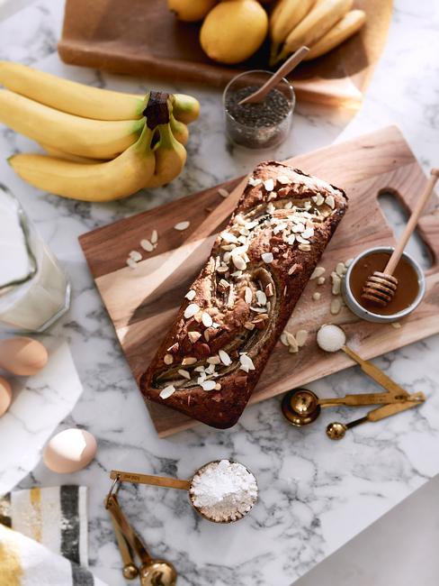 Chlebek bananowy na drewnianej tacy w na marmurowym blacie z obok skadnikw potrzebnych do jego wykonania