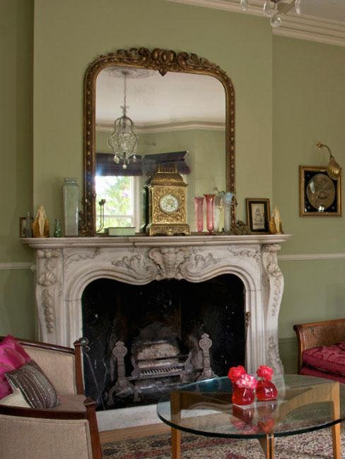 tradycyjny kominek z barokowym lustrem w złotej ramie