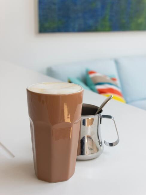 Wysoka, brązowa szklanka z chai latte, na białym blacie