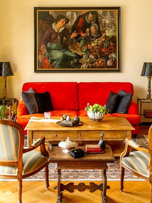 salon w stylu pałacowym z czerwoną sofą, rustykalnym stolikiem kawowym z drewna i obrazem na ścianie