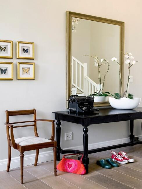 Przedpokój z lustrem w złotej ramie, drewnianym krzesłem i czarnym stoliczkiem oraz galerią ścienną