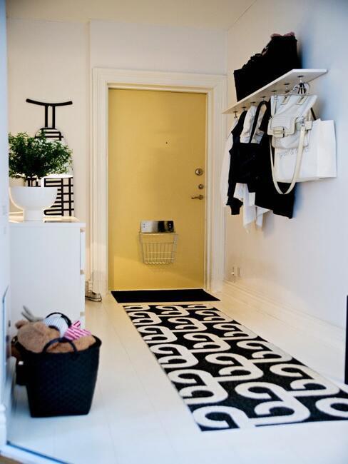Biały przedpokój z żółtymi drzwiami, długim czarno-białym chdnikiem, białą komodą i czarnym koszem