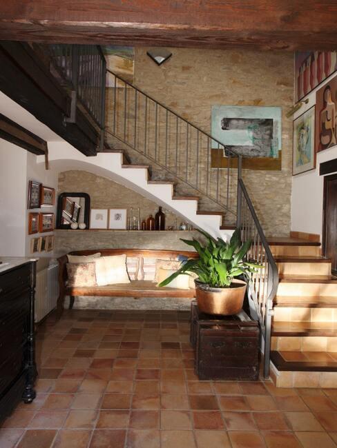 Przedpokój z klatką schodową w domku jednorodzinnym z czarną komodą, czarną szafką z rośliną oraz drewnianą ławką