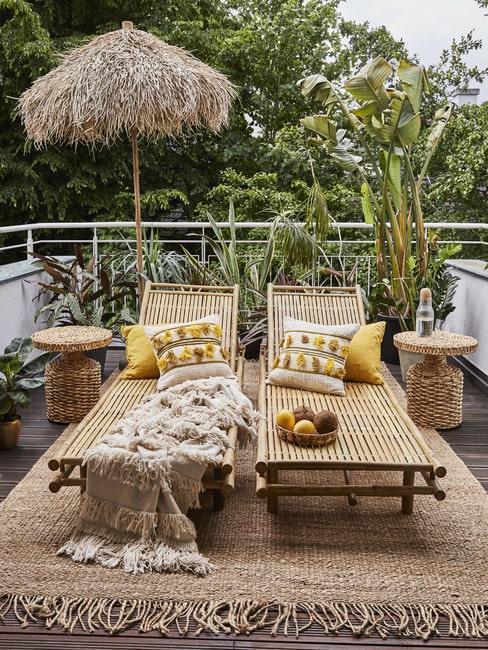 Balkon z dwoma leżakami z bambusa, parasol oraz jutowy dywan zewnętrzny z roślinami