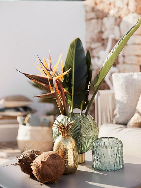 zielony szklany wazon z tropikalnymi liśćmi, złotym ananasem i orzechami kokosa na tarasie