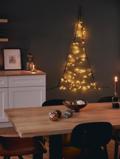 Wnętrze jadalni z czarnymi ścianami, drewnianym stołem, białymi szafkami oraz choinką z lampek