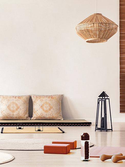 Jasny pokój do jogi z matą na podłodze i orientalnymi poduszkami pod ścianą