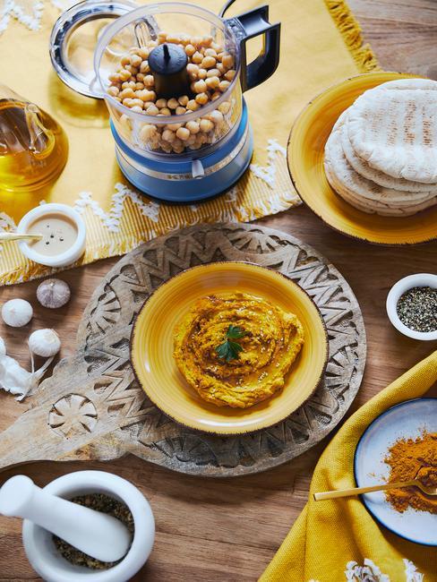 Hummus na żółtym talerzyku obok robota kuchennego na drewnianej desce.