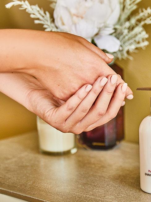 zbliżenie na dłonie, które wmasowują krem do rąk na tle wazonu w łazience