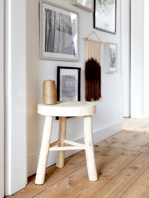 Zbliżenie na biały, drewniany stołek oraz galerię obrazków w przedpokoju w stylu skandi