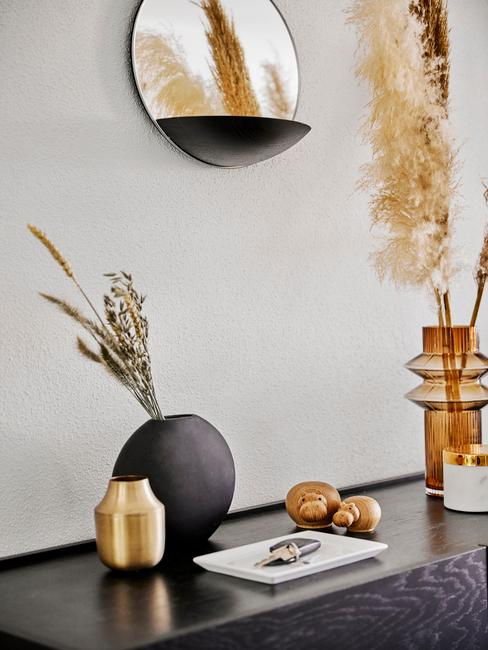 Czarna komoda z wazonem z suszonymi kwiatami, dekoracjami i lustrem