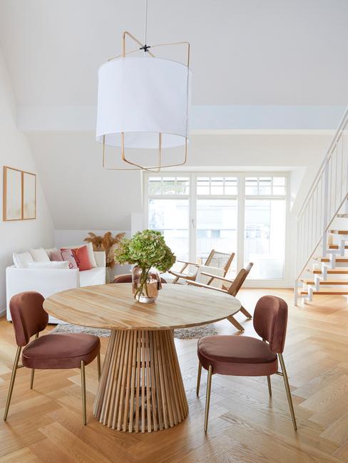 Wnętrze mieszkania w stylu skandynawskim z okrągłym, drewnianym stołem, dwoma krzesłami oraz białą sodą w salonie
